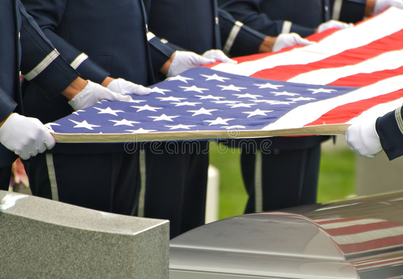 Flag and Country. Horizontal photo of Arlington National Cemetery honor guard holding US flag over casket with flag reflected in casket stock photos
