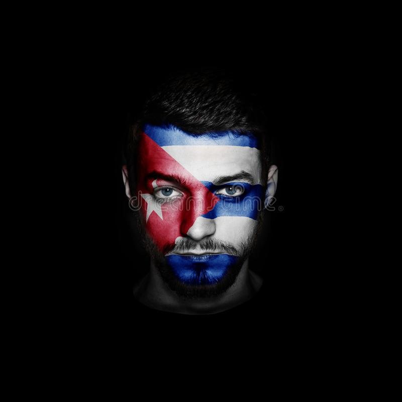 Flag of Cuba painted on a face of a man. stock photos