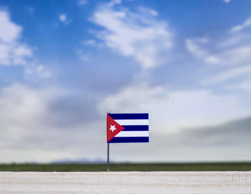Flag of Cuba with vast meadow and blue sky behind it. royalty free stock photos