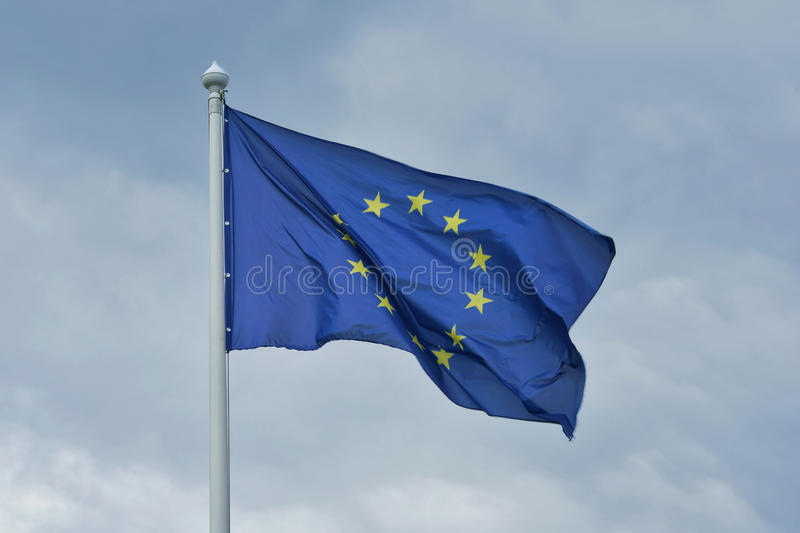 The flag of the European Union flutters on wind. The flag of the European Union flutters on wind, in cloudy day, on the background of gray clouds stock image