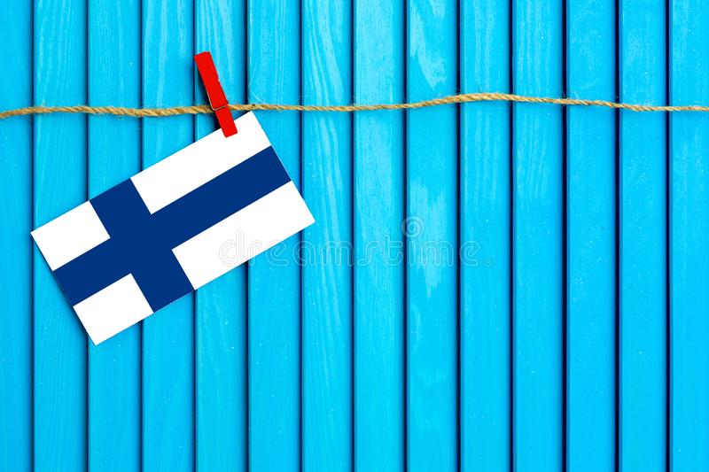Flag of Finland hanging on clothesline attached with wooden clothespins on aqua blue wooden background. National day concept stock photo