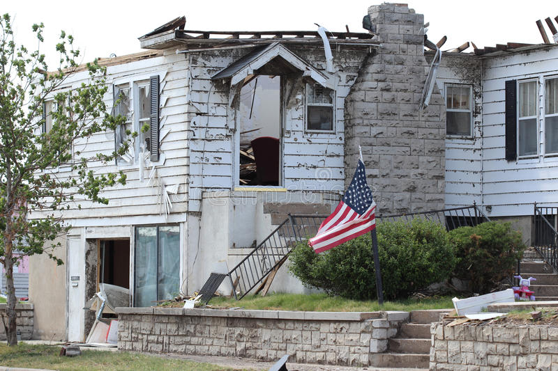 Flag Flies In Front Of Tornado Damage Home. Severe Tornado Damages Home but the owners refuse to give into dispare and fly a flag found in the rubble to stock images