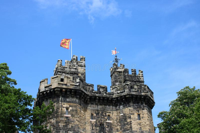 Flag flying John O Gaunt Gateway, Lancaster Castle. View of the top part of John O`Gaunt Gateway with a flag flying and a weather vane. The gateway is now the royalty free stock photo