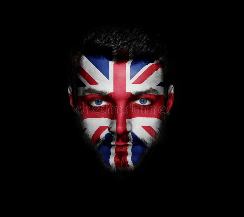 Flag of Great Britain painted on a face of a man. royalty free stock image