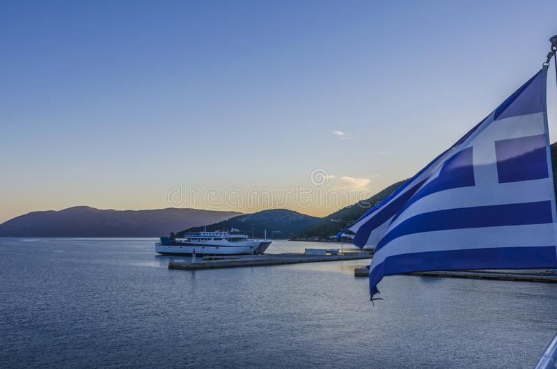 The greece flag flies in Sami harbor on the island of Kefalonia. The flag of greece waving a ferry moored in the Sami Port the Ionian Sea and the mountains of stock images