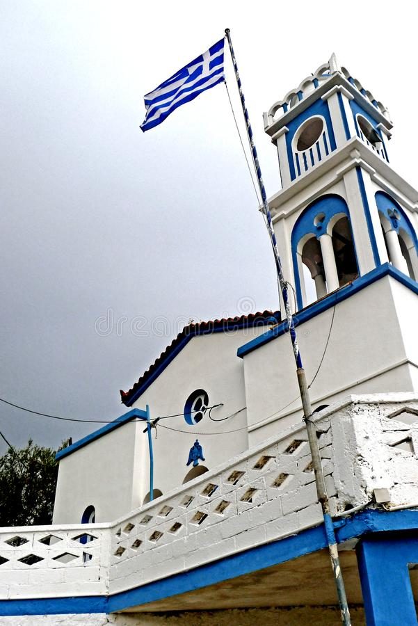 A flag and Greek bell tower in Samos Greece. The green and lush Samos island is located in the northern part of the Aegean Sea, just a few meters from the coast stock images