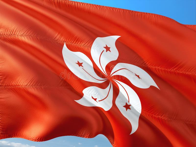 Flag of Honk Kong waving in the wind against deep blue sky. High quality fabric stock photography