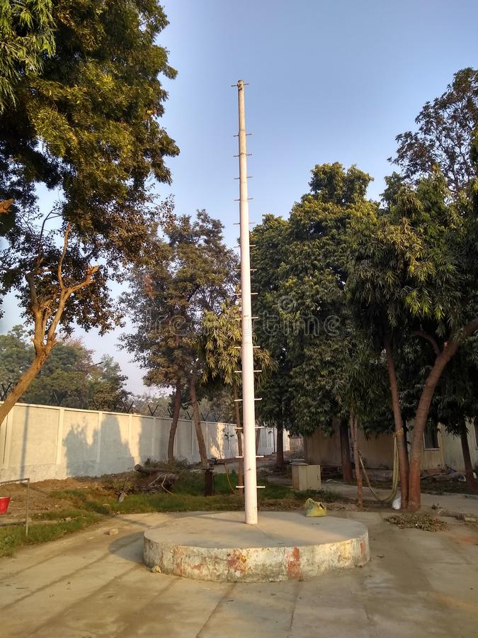 Flag hosting pole at Govt office. The hoist edge is reinforced carves with eyelets designed to attach the flag to the pole. Waiting for republic Day royalty free stock photo