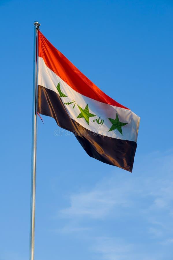 Flag of iraq. On a pole against blue sky stock photos