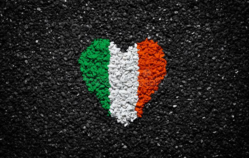 Flag of Ireland, Irish flag, heart on the black background, stones, gravel and shingle, textured wallpaper, valentine`s day royalty free stock images