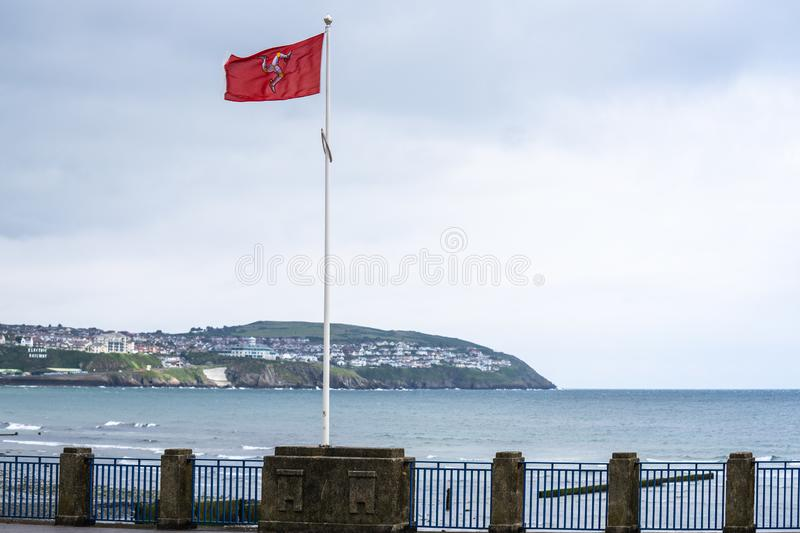 The flag of the Isle of Man or flag of Mann is a triskelion, composed of three armoured legs with golden spurs, upon a red. Background royalty free stock image