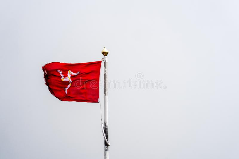 The flag of the Isle of Man or flag of Mann is a triskelion, composed of three armoured legs with golden spurs, upon a red. Background stock photo