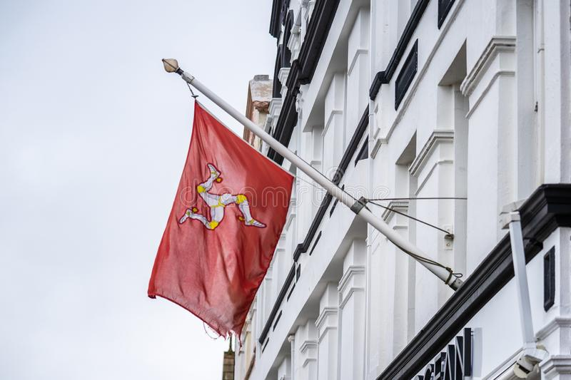 The flag of the Isle of Man or flag of Mann is a triskelion, composed of three armoured legs with golden spurs, upon a red. Background royalty free stock photography