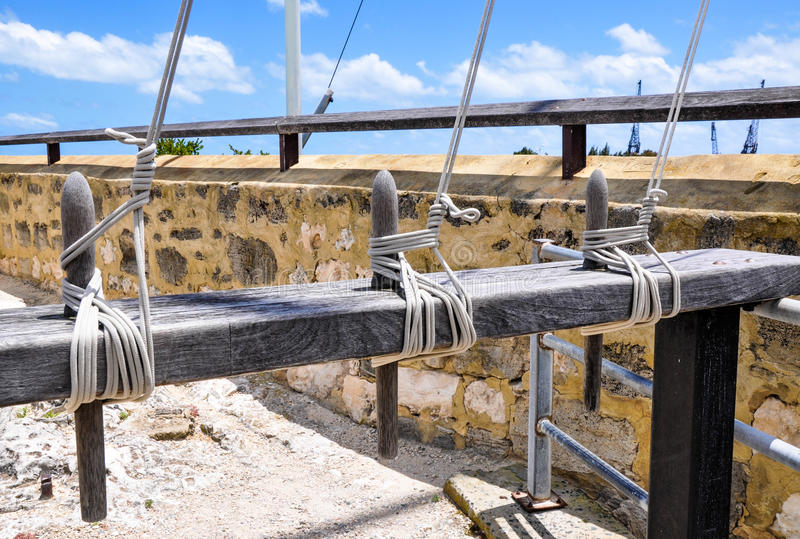Flag Lines and Cleats. Three sets of flag lines with cleats on a wooden posts with knotted tense ropes with a limestone wall backdrop and blue sky stock photography
