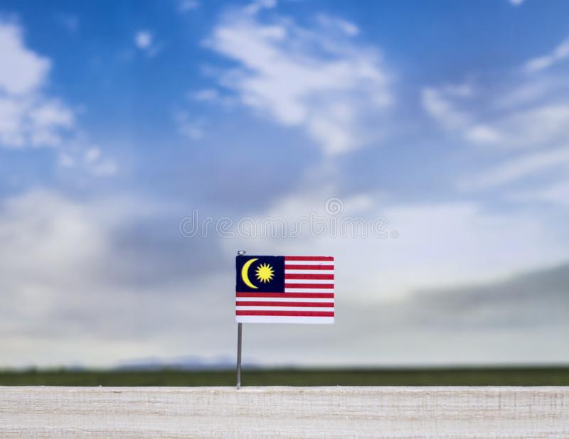 Flag of Malaysia with vast meadow and blue sky behind it. royalty free stock photography