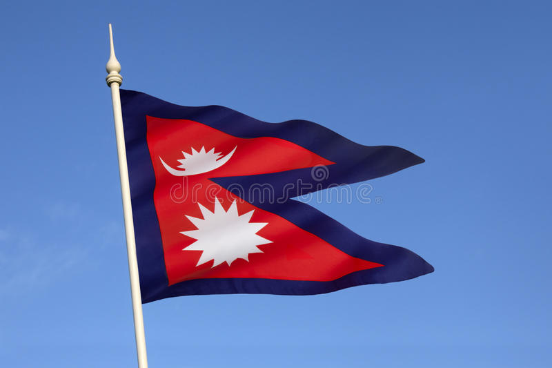 Flag of Nepal. The national flag of Nepal is the worlds only non-quadrilateral national flag. Until 1962, the flags emblems, the sun and the crescent moon, had royalty free stock photography