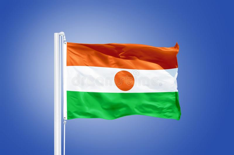 Flag of Niger flying against a blue sky royalty free stock photos