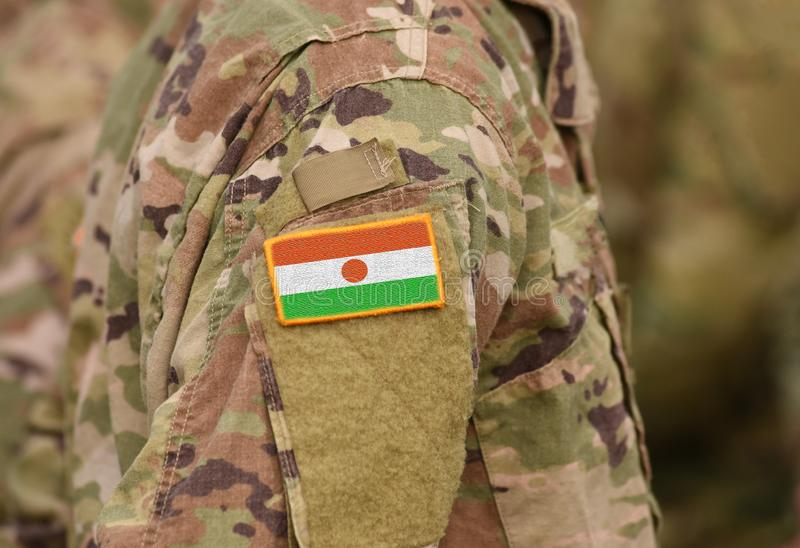 Flag of Niger on soldiers arm collage. Flag of Niger on soldiers arm. Flag of Niger on military uniforms. collage stock photography