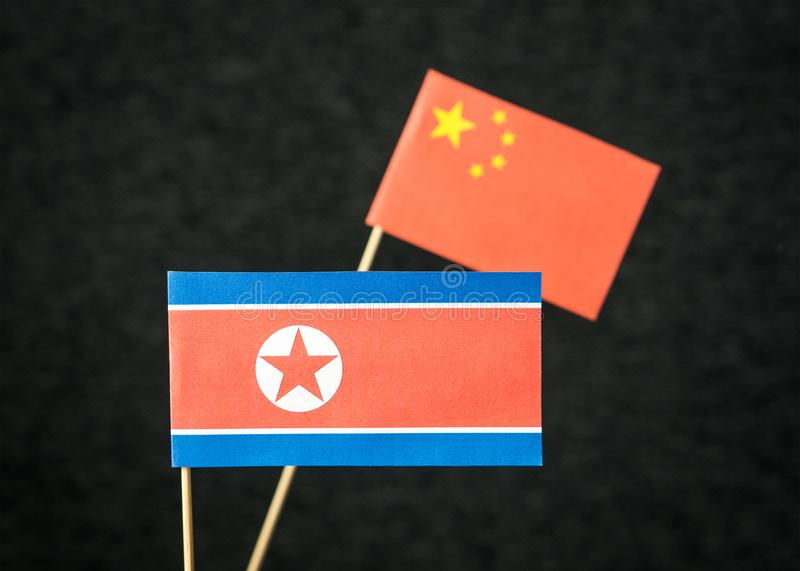 The flag of North Korea and China made from paper. The flag of North Korea and China made from paper on wooden stick against dark background royalty free stock photos