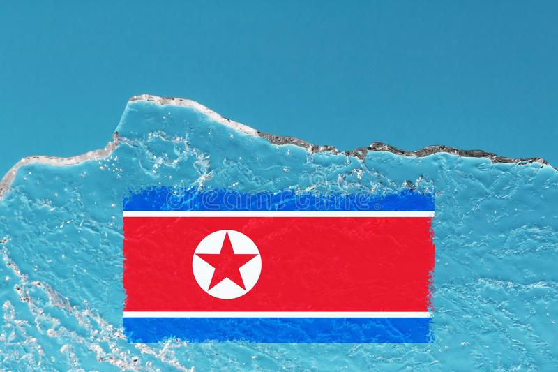 The flag of North Korea is painted on piece of ice in the form of an arctic iceberg against a blue sky. Closed policy, cold war. The flag of North Korea is royalty free stock image