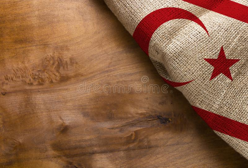 Flag of Northern Cyprus from rough fabric. On a wooden surface stock photo