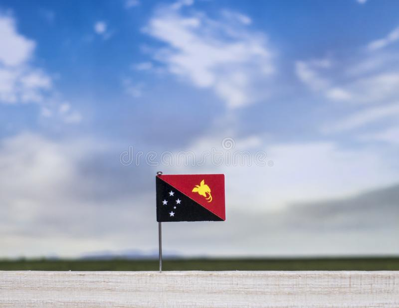Flag of Papua New Guinea with vast meadow and blue sky behind it. royalty free stock photography