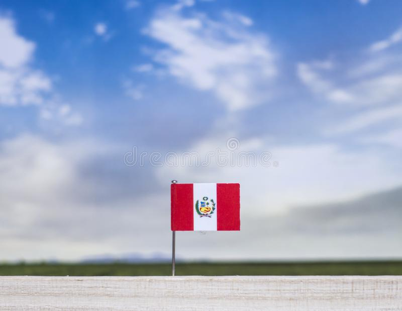 Flag of Peru with vast meadow and blue sky behind it. royalty free stock images