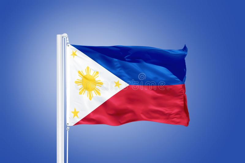 Flag of Philippines flying against a blue sky.  stock photo