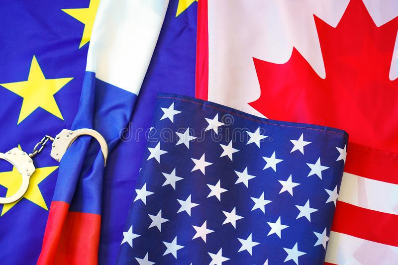 European Union, Canada, USA. The concept of sanctions for Russia. Flag of Russia in Handcuffs on the background of the European Union and Canada and United royalty free stock image