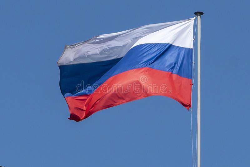 Flag of Russia, the Russian Federation, the tricolor against the blue sky develops in the wind. Close-up stock photography