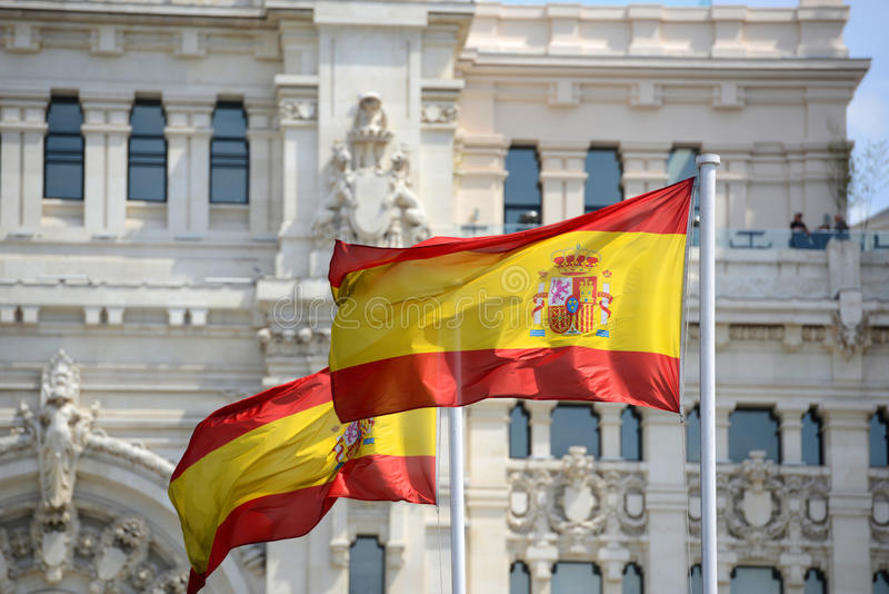 Flag of Spain in the wind. In front of Palace of Communication (Spanish: Palacio de Comunicaciones) in Madrid, Spain royalty free stock photo