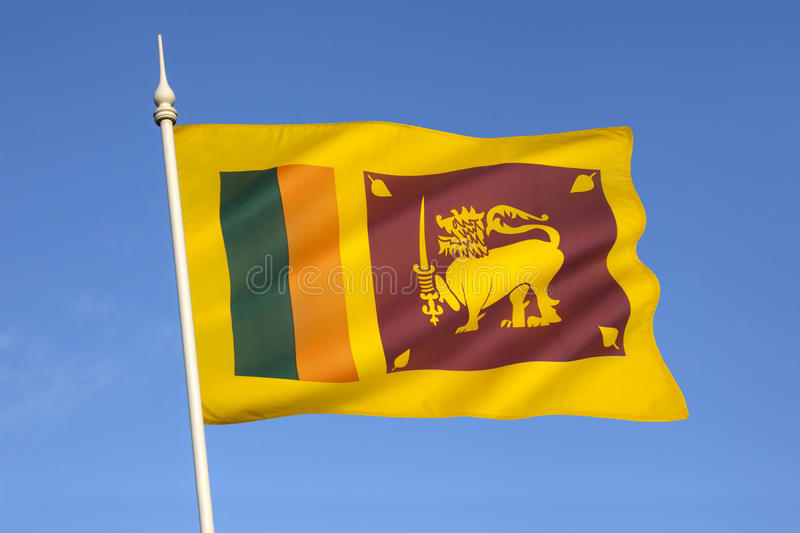Flag of Sri Lanka. The flag of Sri Lanka consists of a gold lion, holding a kastane sword in its right fore paw on a dark red background with four golden bo royalty free stock images