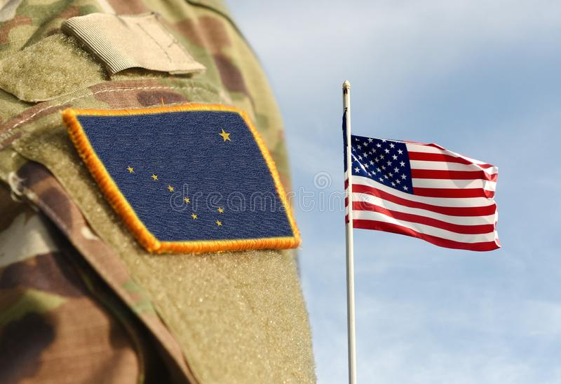Flag of State of Alaska on military uniform and Flag of USA weaving in the sky stock images