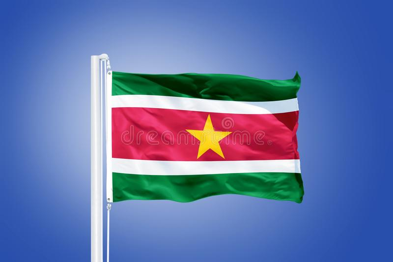 Flag of Suriname flying against a blue sky.  stock photography