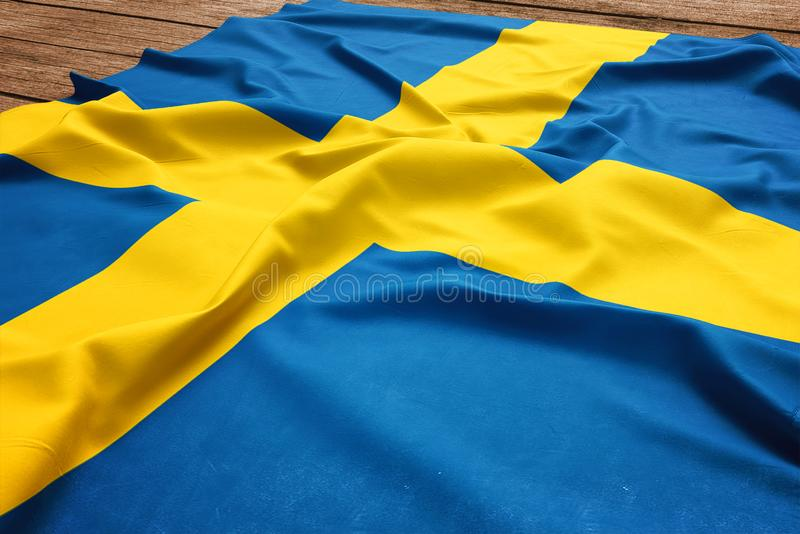 Flag of Sweden on a wooden desk background. Silk Swedish flag top view.  royalty free stock image