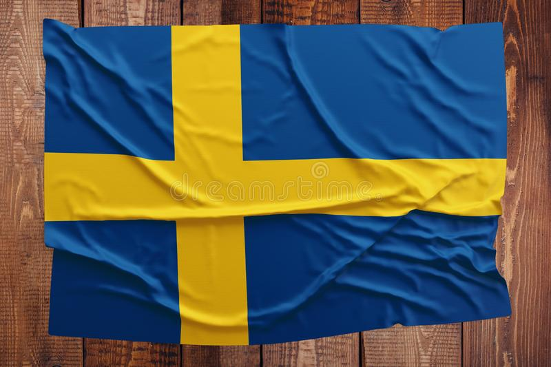 Flag of Sweden on a wooden table background. Wrinkled Swedish flag top view.  royalty free stock photos
