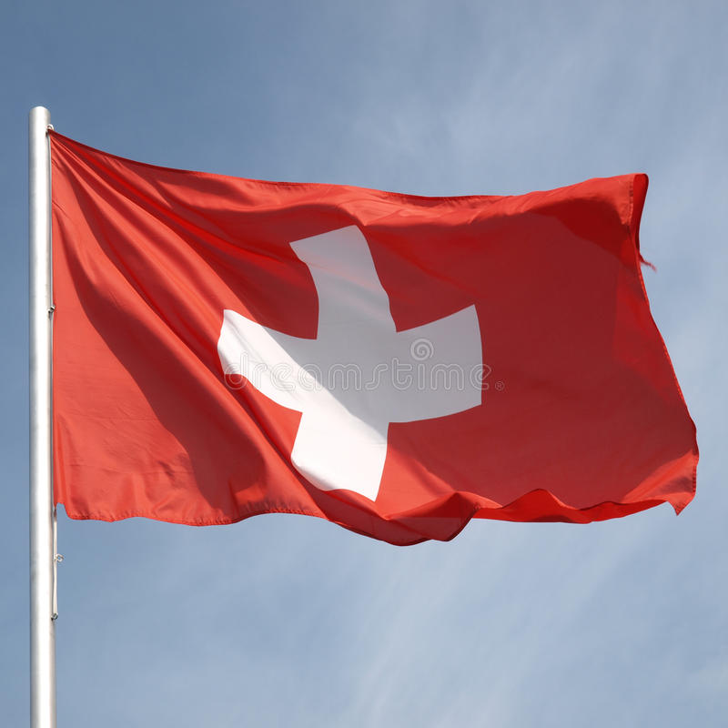 Flag of Switzerland. Over a blue sky royalty free stock images