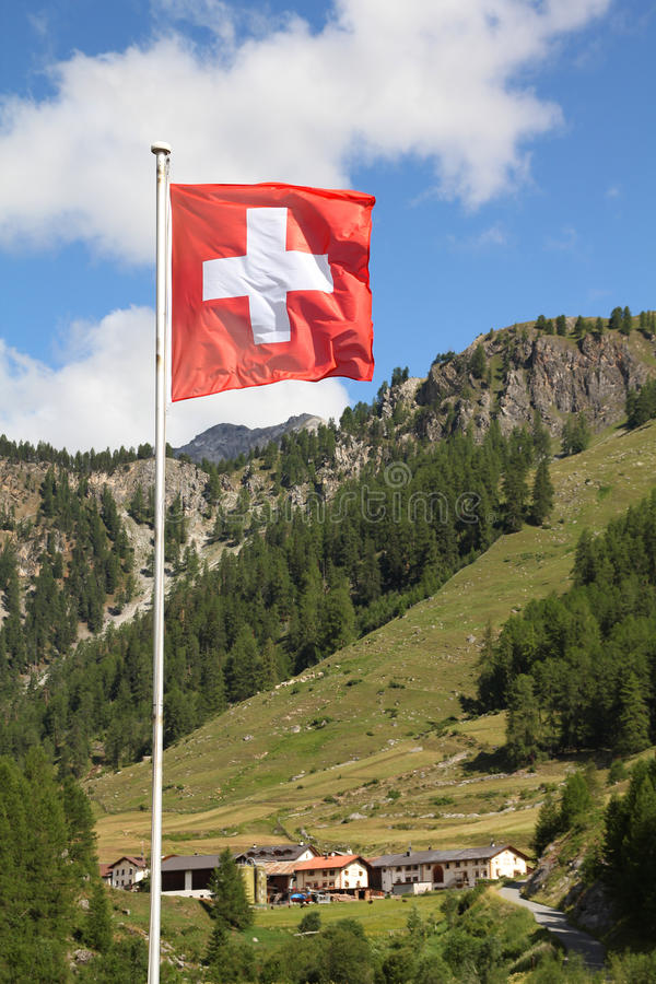 Flag of Switzerland. Swiss flag - national symbol of Switzerland with Alps in background. Graubunden canton (Grisons royalty free stock photo