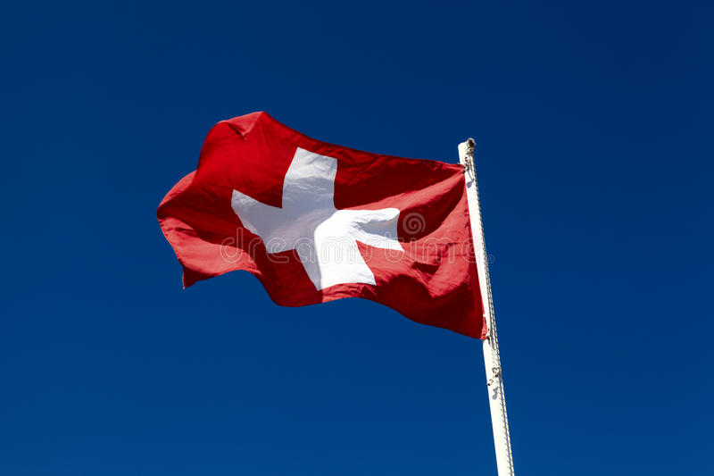 Flag of Switzerland. Is waving on the sky background royalty free stock photo