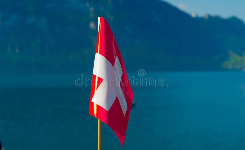 Flag of Switzerland against the backdrop of the mountains near Lake Lucerne. Flag of Switzerland against the backdrop of the mountains near Lake Lucerne stock photography
