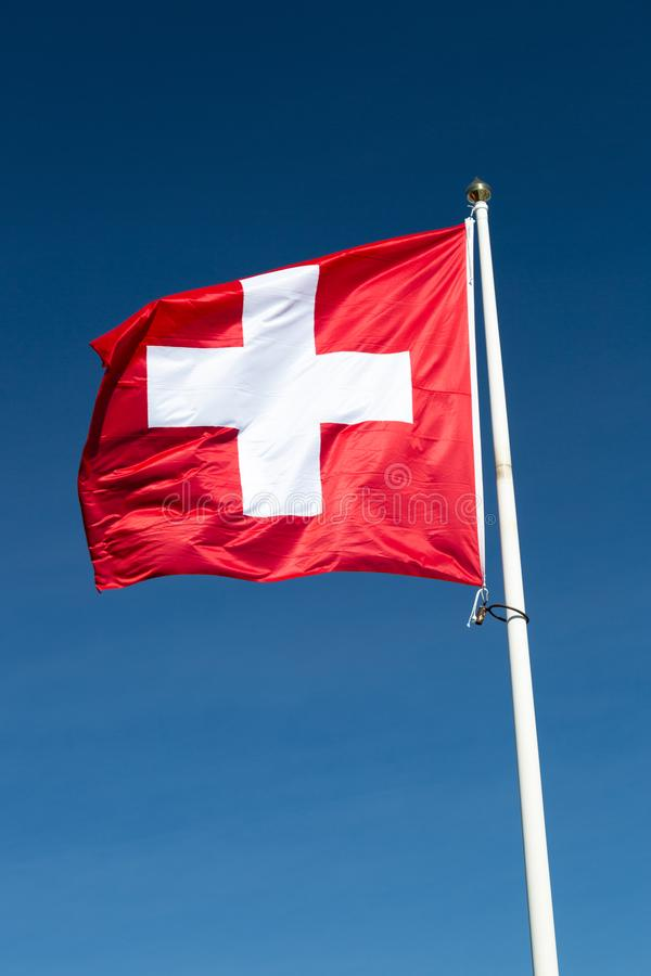 The Flag of Switzerland with a blue sky.  royalty free stock image