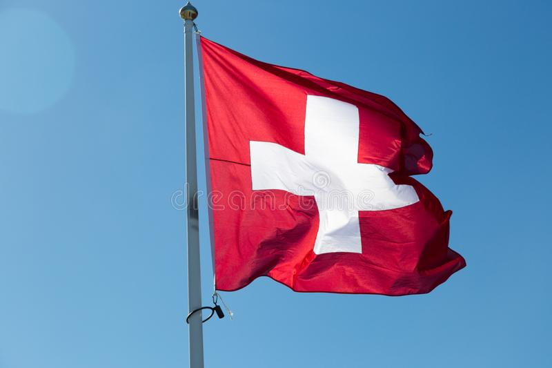 The Flag of Switzerland with a blue sky.  stock image