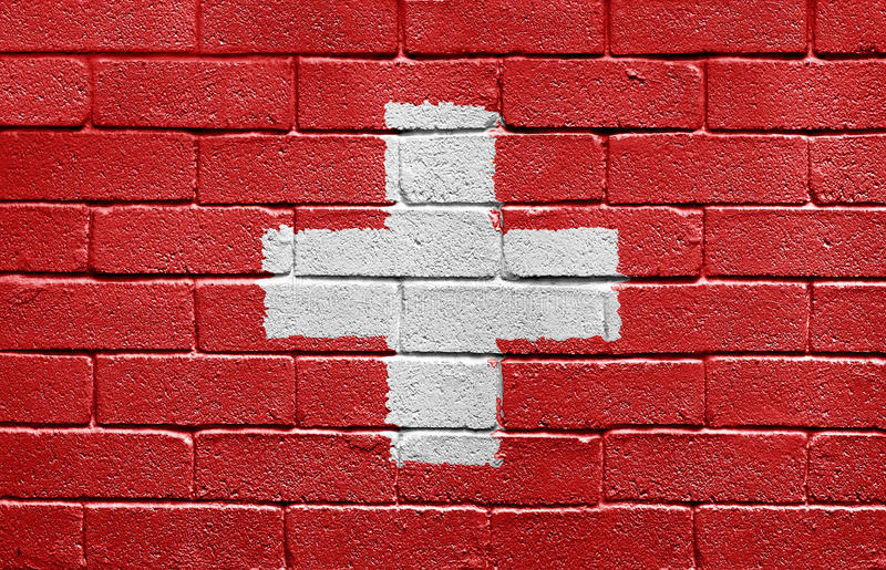 Flag of Switzerland on a brick wall. Flag of Switzerland painted onto a grunge brick wall royalty free stock photos