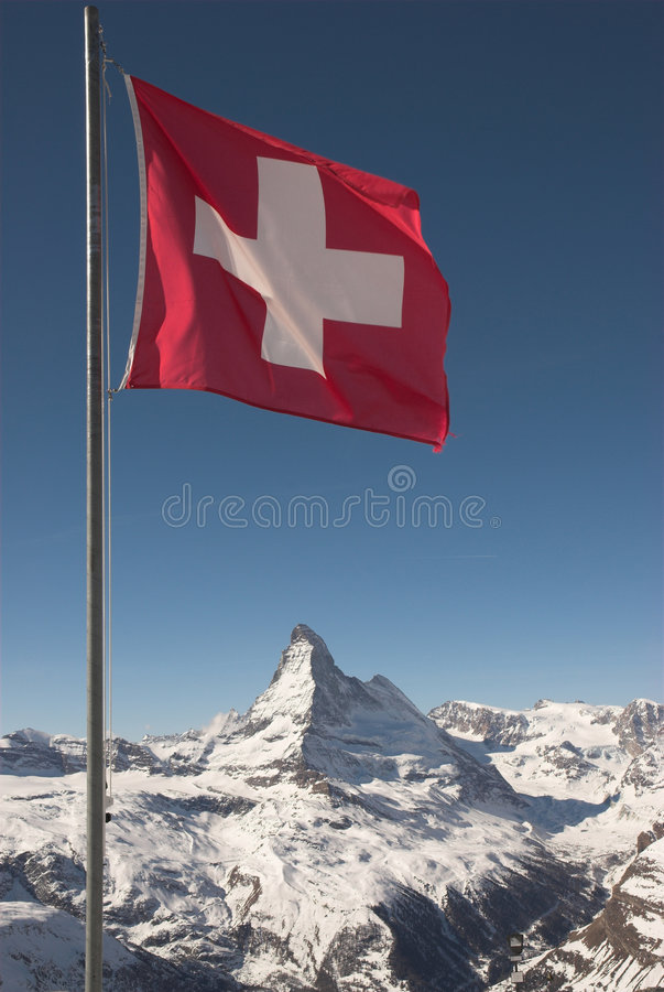 Flag of Switzerland on mountaintop. A mountaintop view of the national flag of Switzerland with the Matterhorn in the background stock photo