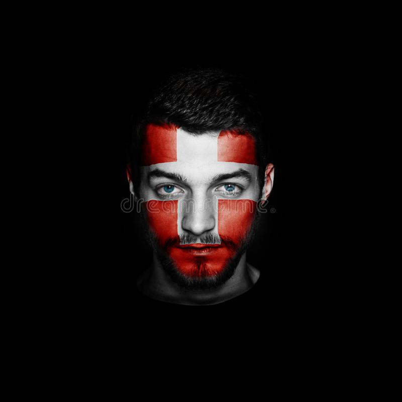 Flag of Switzerland painted on a face of a man. Flag of Switzerland painted on a face of a man on black background stock photo