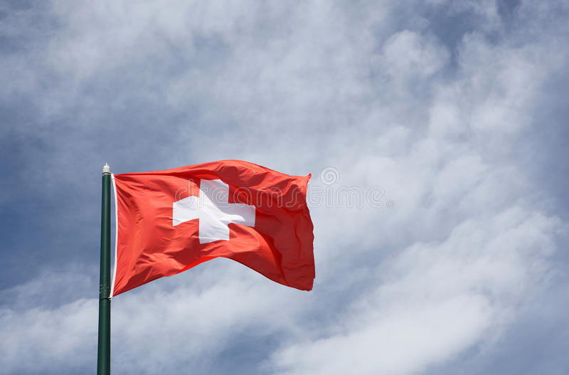 Flag of Switzerland. On a sky and clouds stock image