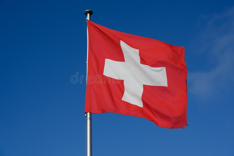 Flag of Switzerland - swiss flag blowing in the wind. White cross on red ground - national flag of Switzerland stock photos