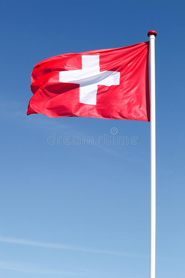 Flag of Switzerland in the sky. Flag of Switzerland waving in the sky stock photo