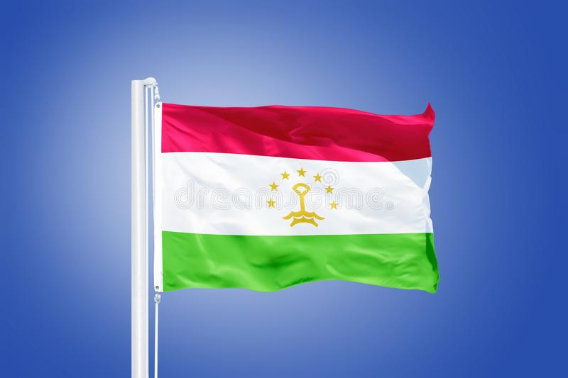 Flag of Tajikistan flying against a blue sky.  stock images