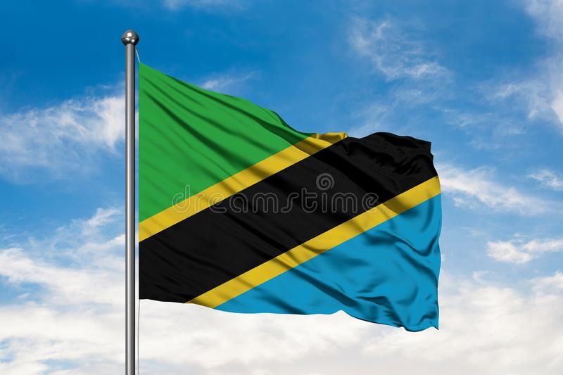 Flag of Tanzania waving in the wind against white cloudy blue sky. Tanzanian flag.  royalty free stock photography